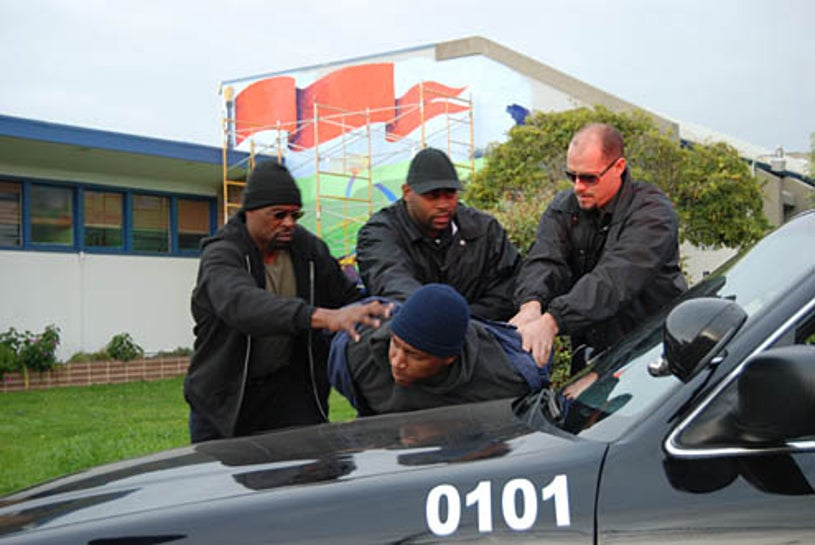 I Almost Got Away with It - Marshall Brown held against police car by Oller
