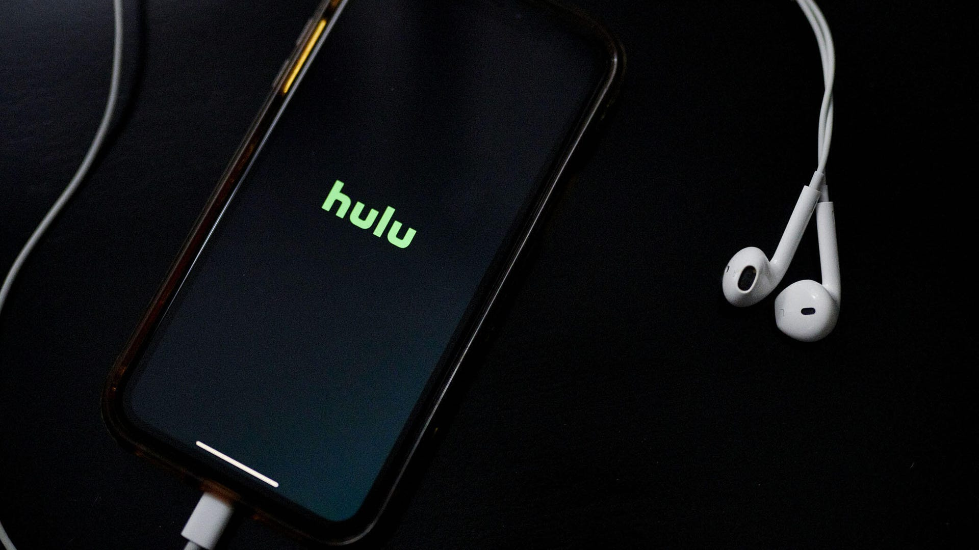 Hulu on a phone with earbuds