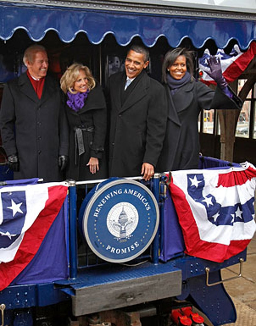 Joe Biden, Jill Biden, Barack Obama and Michelle Obama wave to members of the news media after boarding their antique Pullman Georgia 300 train car in Wilmington, Delaware, January 17, 2009