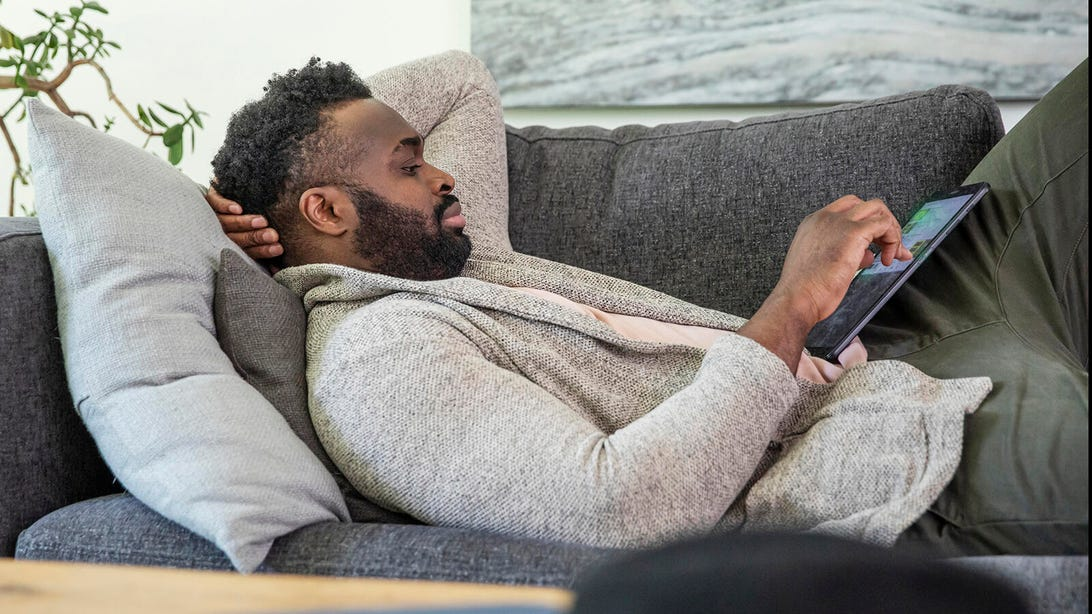 Man watching Hulu on computer on couch
