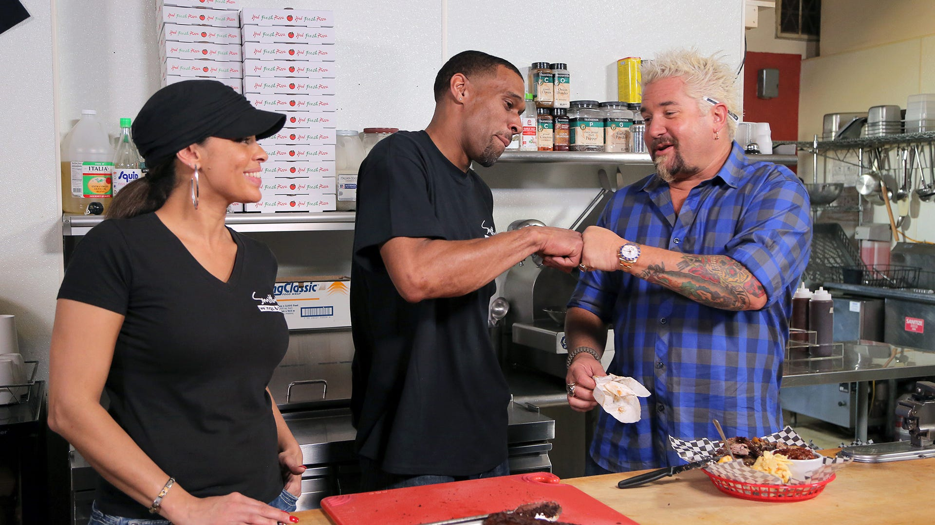 Jamie Smith and Steve Smith, co-owners of Smitty's Wings & Things in Stockton, California, and host Guy Fieri, Diners, Drive-Ins and Dives